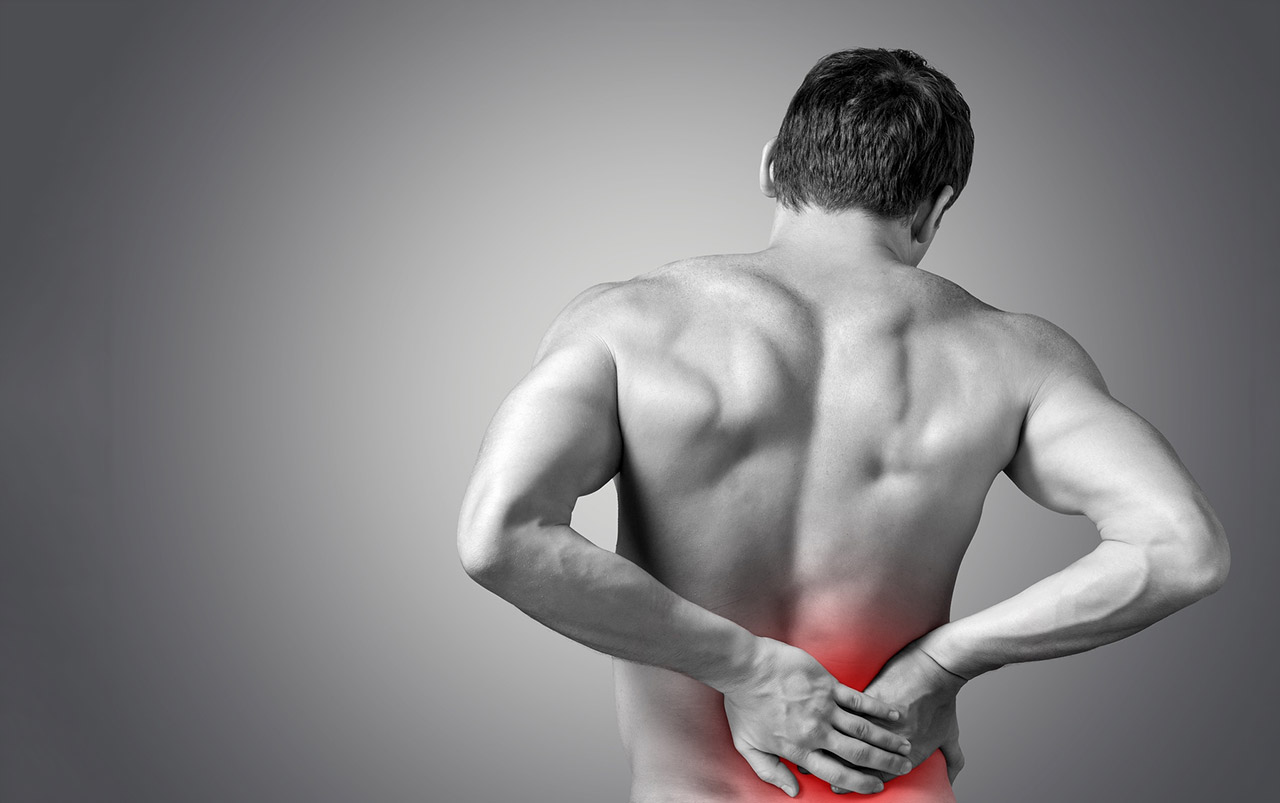 Man holding back who needs back pain treatment